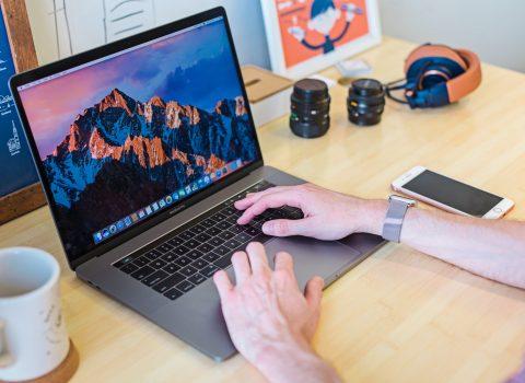 Web designer's workspace with laptop, phone, and coffee mug